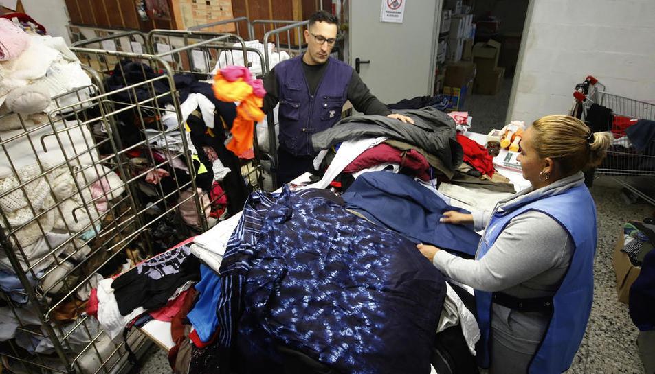 Treballadors de Troballes, ahir, a la planta que tenen a Gardeny, on reben la roba que els lleidatans deixen als contenidors.