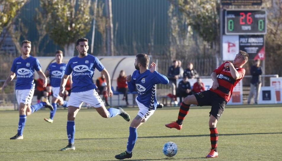 Un jugador de l'EFAC Almacelles intenta controlar la pilota davant de dos rivals del Rapitenca.