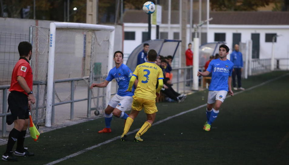 Un jugador del Lleida Esportiu B pugna amb la pilota davant d'un del Vila-seca sota l'atenta mirada de l'assistent arbitral.