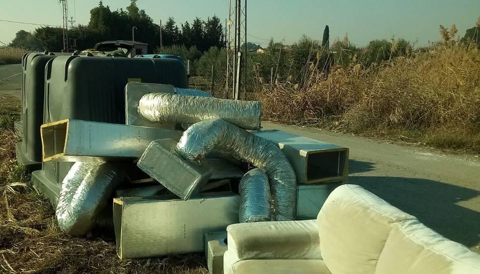Un sofà i extractors amb conductes abocats al Camí de la Mariola.
