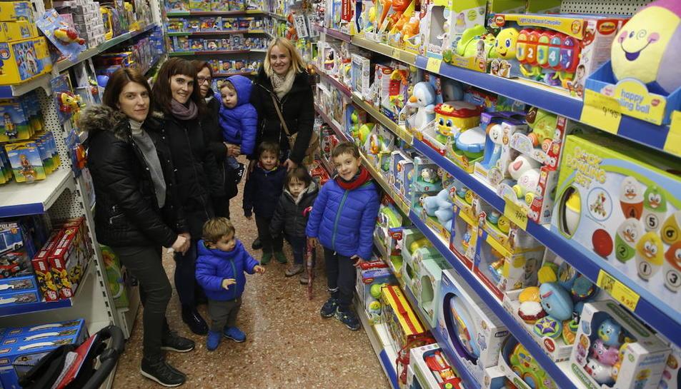 Compradors, petits i grans, comparant joguets ahir en una botiga de la Zona Alta.