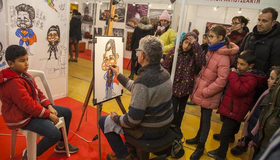 Un dels artistes que participen en la mostra dibuixant la caricatura d'un nen.