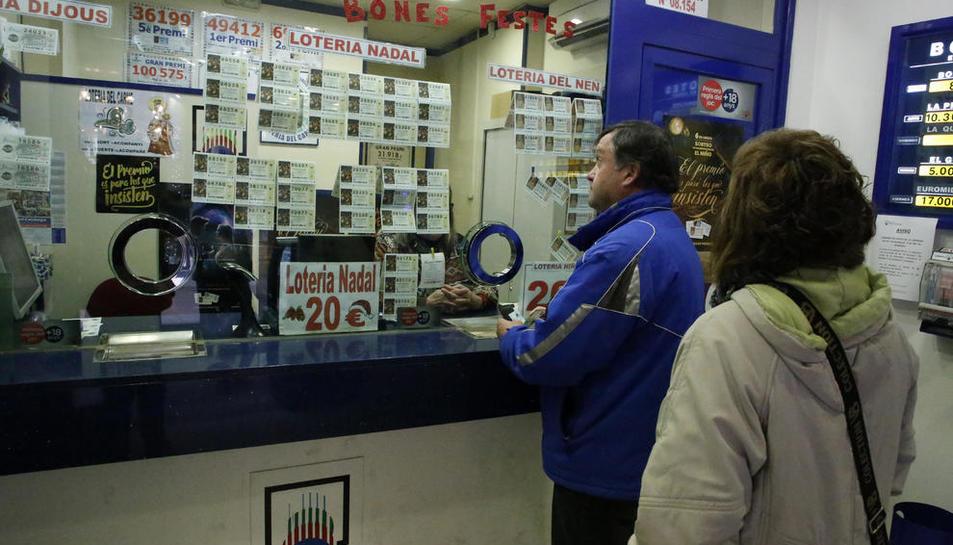 Clients ahir triant el número a l'administració de loteria del carrer del Carme de Lleida.