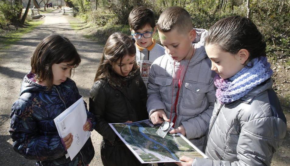 Un grup de nens consulta un mapa de la Mitjana durant l'activitat.
