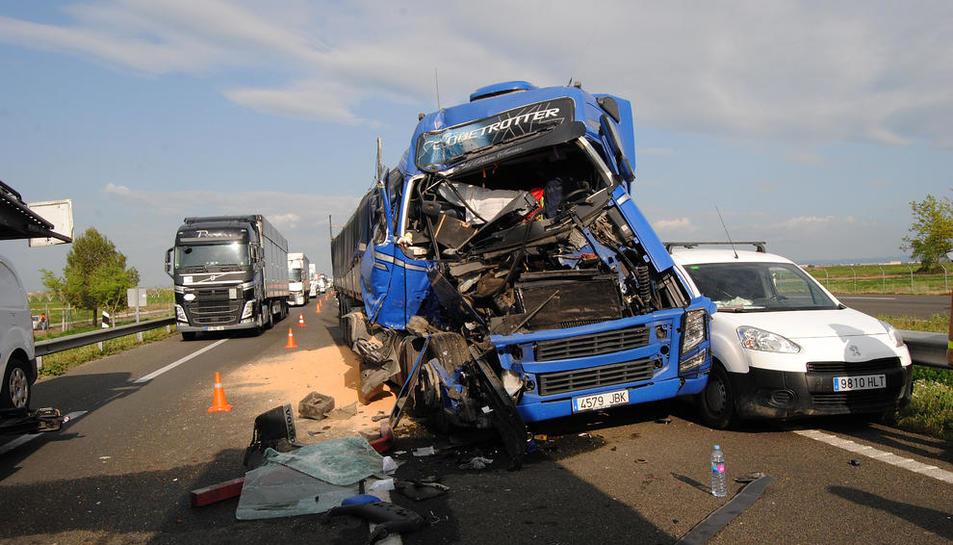 Imagen de uno de los camiones implicados y al lado, la cola de vehículos.