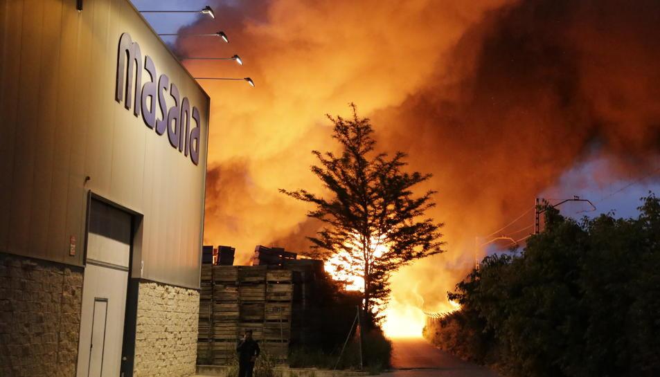 Un espectacular incendi calcina palots i una nau al polígon i talla la via del tren