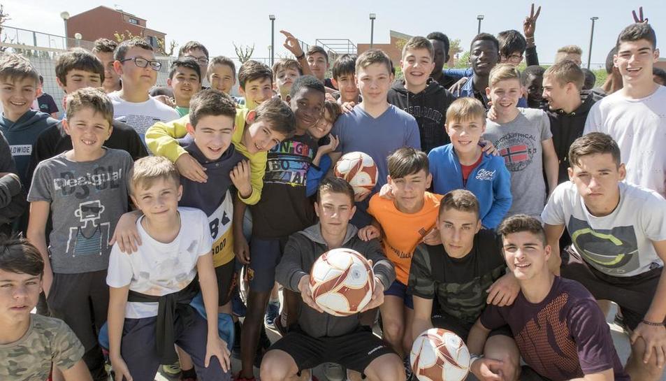 Un grup d'alumnes de l'institut amb pilotes. I és que el futbol serveix com a instrument per unir-los a tots.