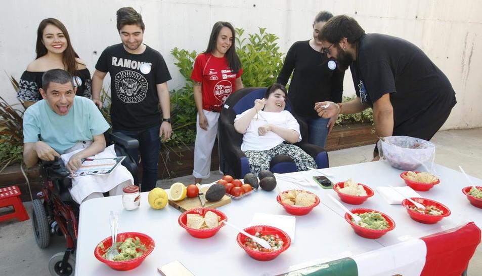 Un estudiante de Educación Social, dando a probar guacamole maxicano a una residente de Aremi.