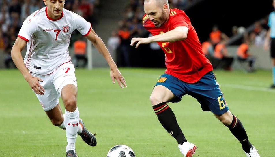 Andrés Iniesta porta la pilota davant de la pressió del jugador de Tunísia, Saif-Eddine Khaoui.