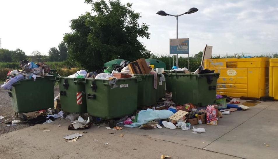 Els contenidors davant la minideixalleria de Castellserà, desbordats ahir al matí.