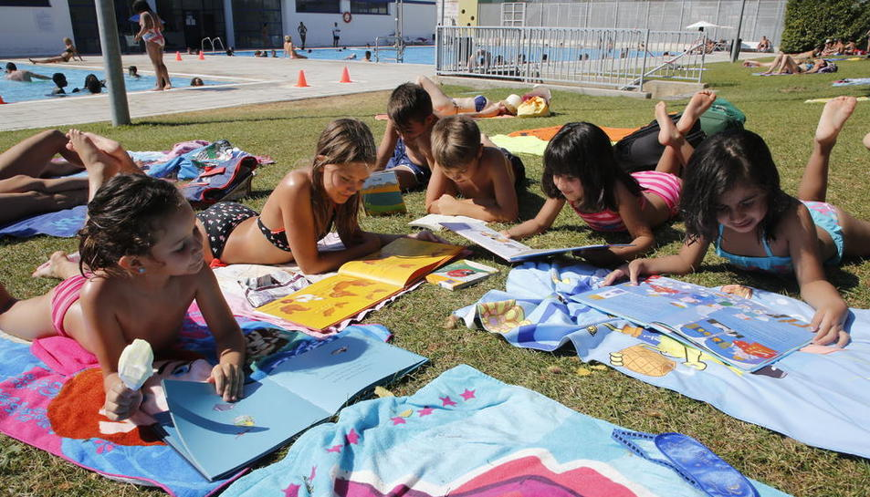 Alguns dels nens que ahir van gaudir de la bibliopiscina de les piscines municipals de Pardinyes, a Lleida.