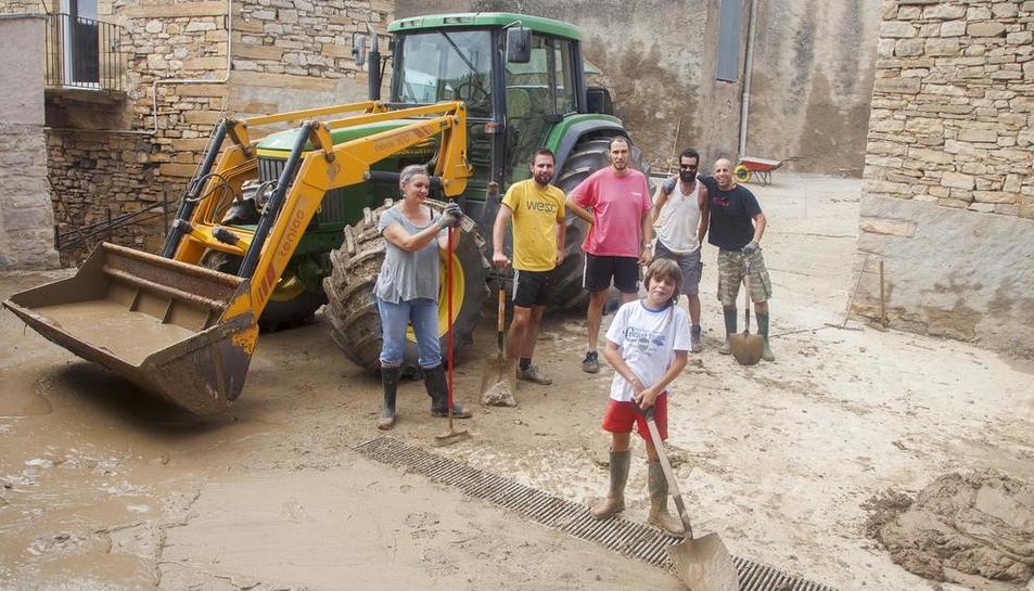 Vecinos de Vilagrasseta, en Montoliu de la Segarra, limpiaban ayer los restos de barro en la plaza de la Iglesia.