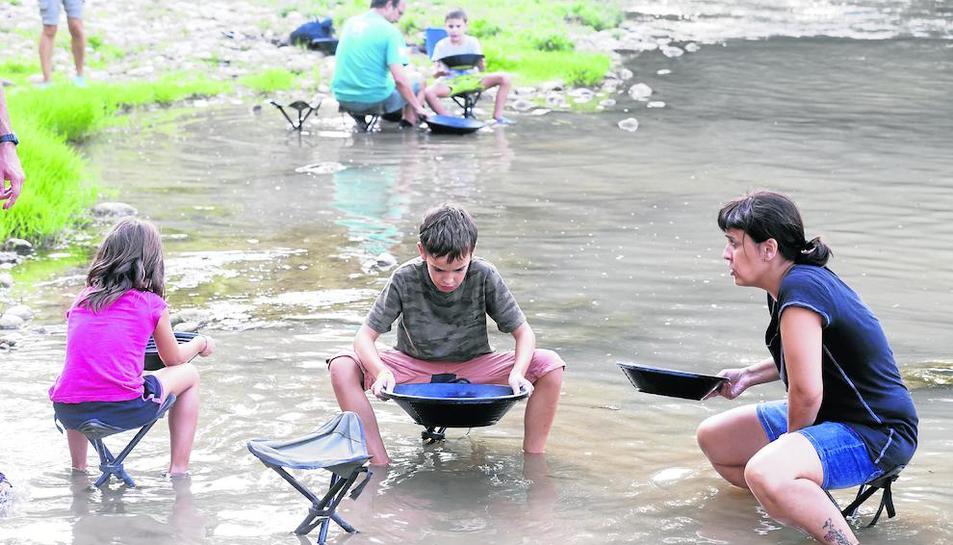 Petits i grans busquen palletes d'or al riu mitjançant l'antic procés de tamisat.