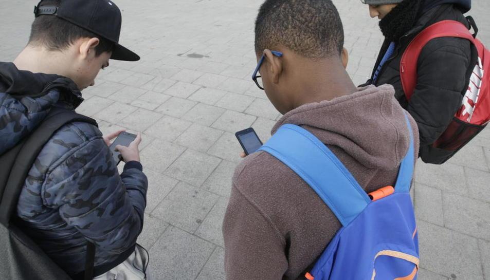 Imagen de archivo de jóvenes utilizando su teléfono móvil.
