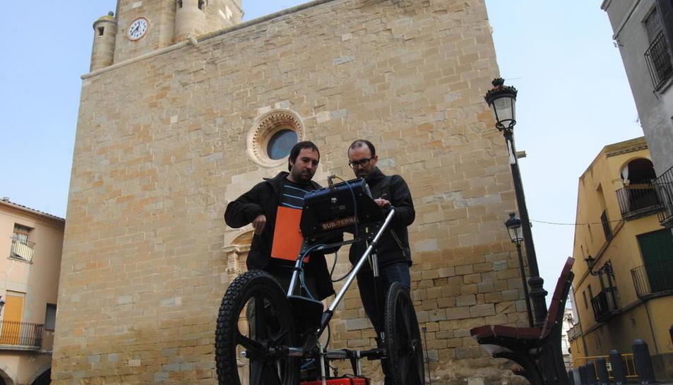 Los geólogos Aritz Urruela y Ruben García, pasando el georadar por la plaza de la iglesia.