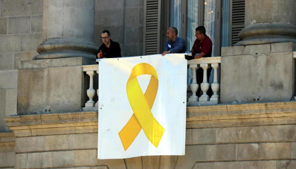 Tres operaris col·loquen de nou el llaç groc a la façana de l'ajuntament de Barcelona.