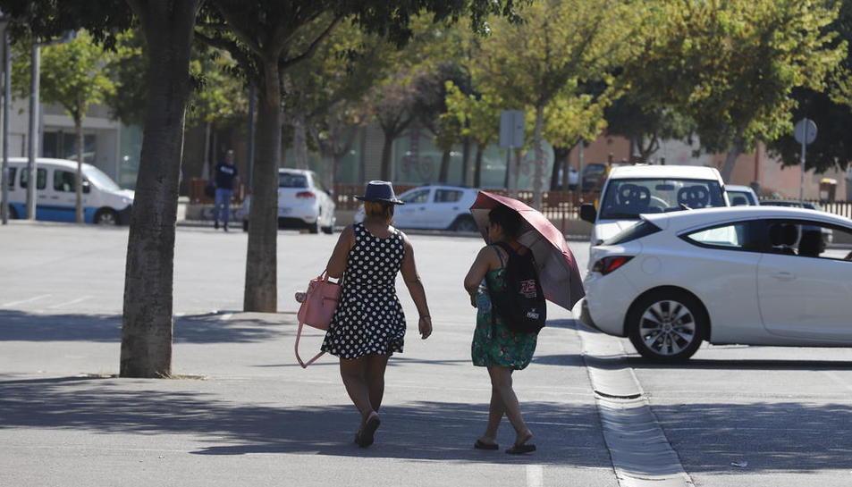 Dos vianants protegint-se del sol a Lleida, on el termòmetre va superar els 34 graus.