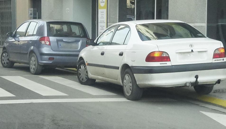 Alguns cotxes envaint un pas de vianants.