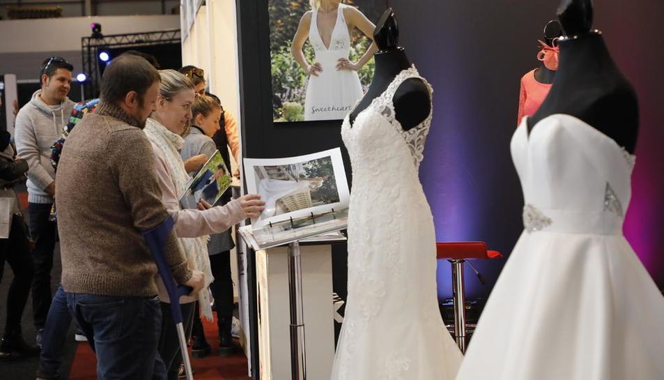 Visitants s'interessen pels catàlegs de vestits de núvia d'un dels expositors de la fira.