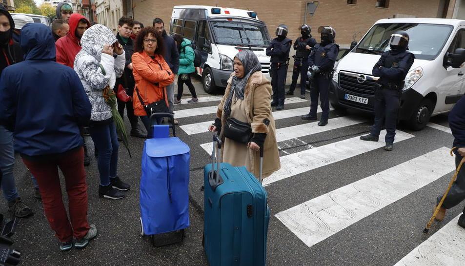 Alguns dels afectats sortint del bloc amb els seus estris personals davant d'efectius dels Mossos.