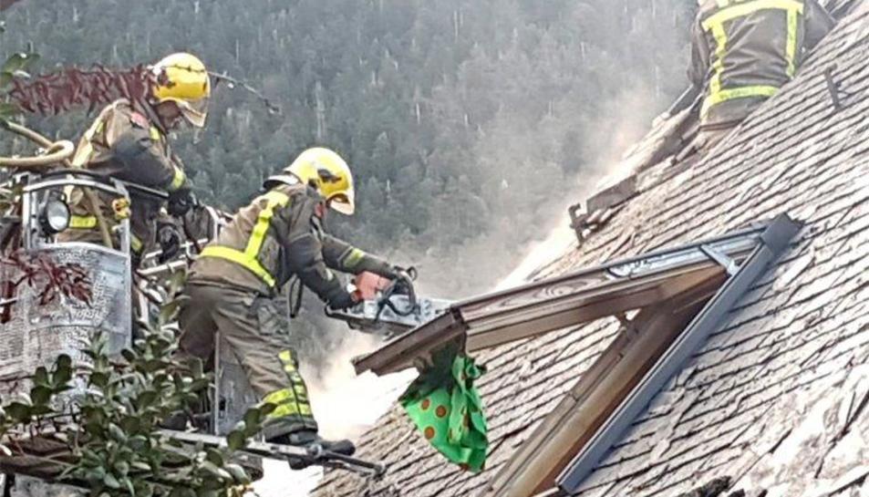 Bombers sufocant les flames originades en una casa adossada.
