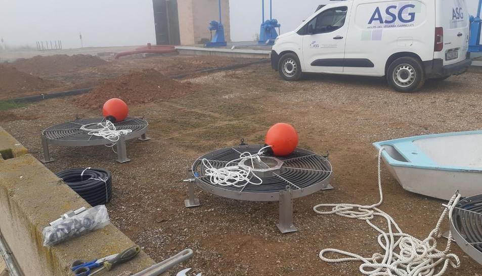 Los trabajos en la balsa de Alfés para instalar el sistema para inyectar aire comprimido en el agua.
