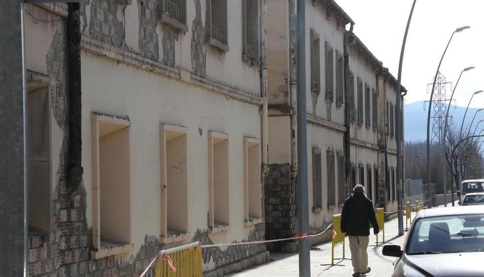 Un hombre junto a las antiguas casas de los ferroviarios, valladas por riesgo de desprendimientos.