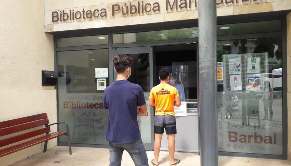 Dos usuaris de la Biblioteca Pública de Tremp esperaven ahir el seu torn per recollir un llibre.