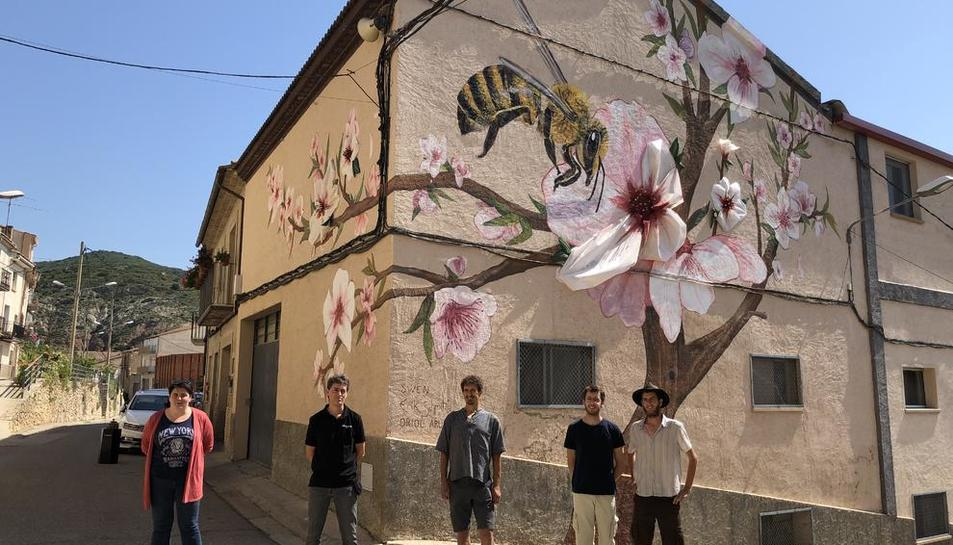 La alcaldesa de Os de Balaguer, el gerente de Torrons i Mel Alemany y los tres artistas ante el mural.