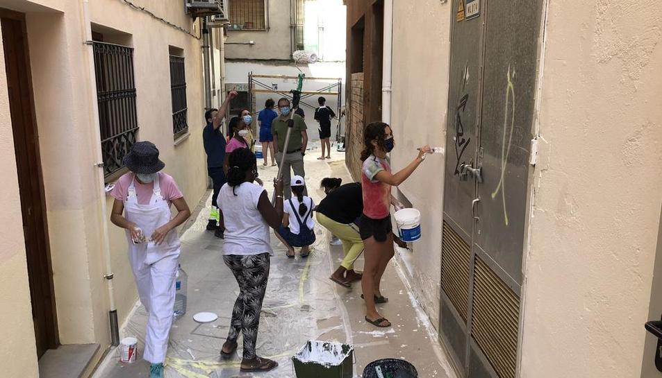 Imatge dels treballs que es duen a terme per pintar façanes al carrer Vilaclosa.