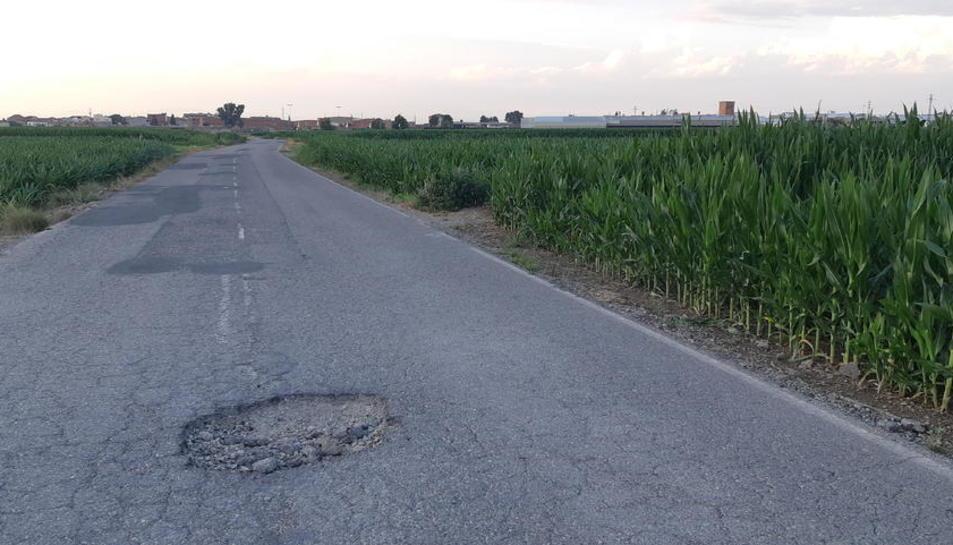 El socavón que había en el camino que conecta Fondarella y Miralcamp y un operario reparándolo.