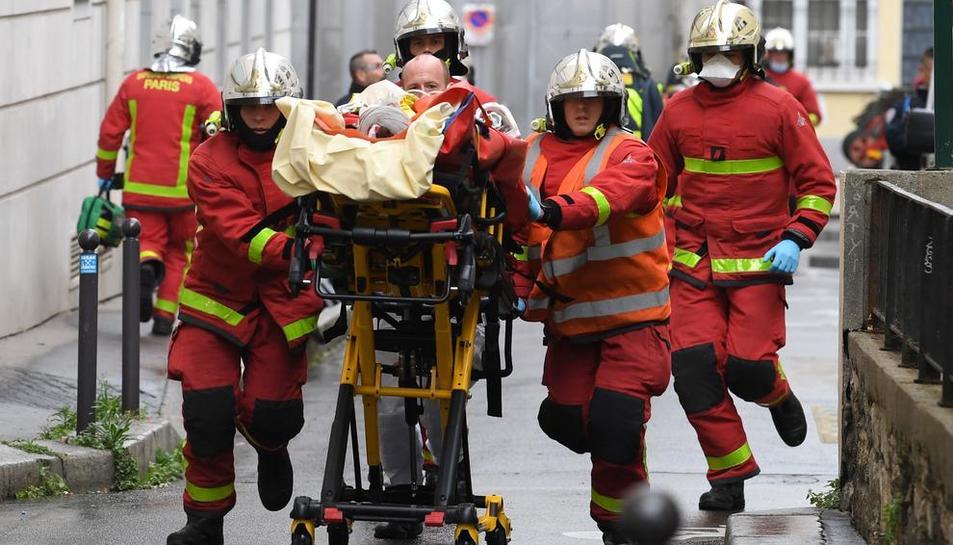 Els serveis d'emergència evacuen un dels ferits en l'atac terrorista d'ahir, a París.