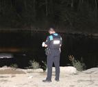 Un urbà ahir a la nit al costat del cotxe, que va quedar submergit al riu a Pardinyes.