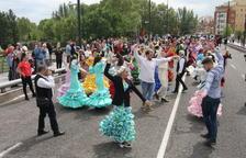 Els participants ballant una sevillana al pont Vell en una cercavila en la qual no van faltar carretes i cavalls.