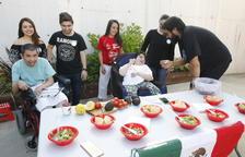 Un estudiant d'Educació Social dona a provar guacamole mexicà a una resident d'Aremi.