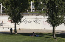 Dos jóvenes se resguardaban ayer del calor a la sombra de los árboles cerca del río Segre.