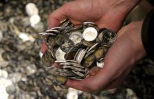 Imagen de una persona con un puñado de monedas de euros.