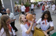 Arriba, una chica bebiendo del agua de Sant Magí en Cervera. A la derecha, la alcaldesa de Tàrrega recibiendo el cántaro conmemorativo.