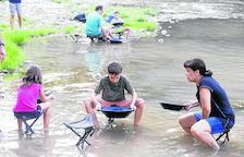 Pequeños y mayores buscan particulas de oro en el río mediante el antiguo proceso de tamizado.
