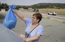 Una veïna diposita les escombraries en un contenidor.