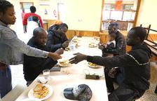 Algunas de las personas desalojadas por el incendio comiendo en la Manreana.