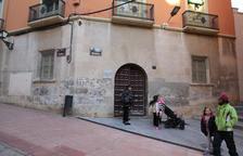 Pares i alumnes a l'exterior de la seu del col·legi Cervantes del carrer Cavallers.