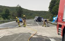 Bomberos limpiando la carretera, que estuvo unas tres horas cortada, y al fondo uno de los turismos implicados.
