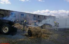 Arden un tractor y varias balas de paja en una granja de Isona