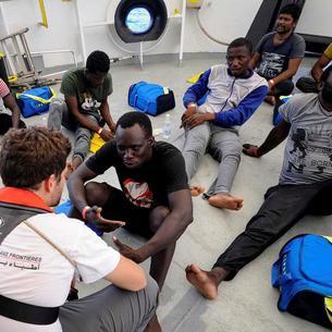 Imatge de migrants amb membres de l'equip de Metges sense Fronteres.