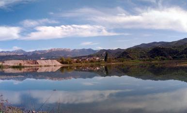 Des de l'horta d'Oliana a la zona de la cua de l'embassament de Rialb, amb l'aigua tranquil·la permetent el reflex de tot el paisatge i cel a l'aigua, un perfecte efecte mirall d'un preciós paisatge primaveral.