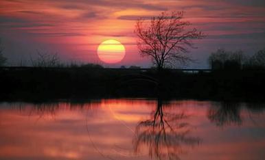 La calma i els núvols prims han donat una posta de sol tranquil·la i amb reflexos en aquest pantà de reg al 100% daigua.
