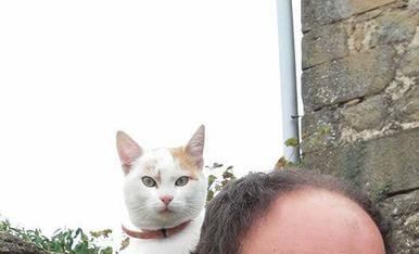 El gat tom al ombro del seu amo Jaume.Sant Climenç de Pinell.foto de Magda Bach.