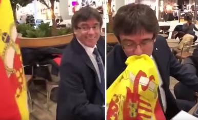 © Puigdemont besant la bandera espanyola