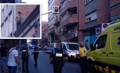 Agents i veïns, amb el carrer tallat. La fletxa indica on és el jove amb l'ampliació del requadre